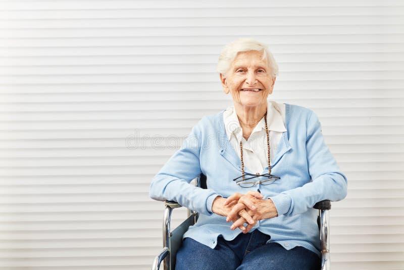 A mulher superior idosa de sorriso está sentando-se na cadeira de rodas imagem de stock