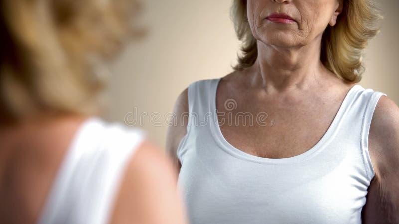 Mulher superior insatisfeita que olha no espelho em seu corpo enrugado, processo de envelhecimento foto de stock royalty free