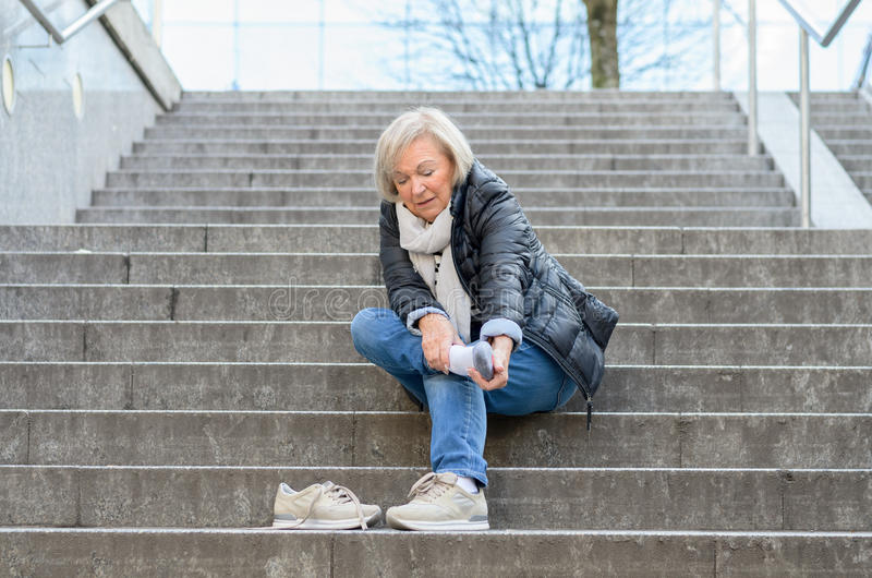 Mulher superior insolúvel que faz massagens seu pé imagem de stock