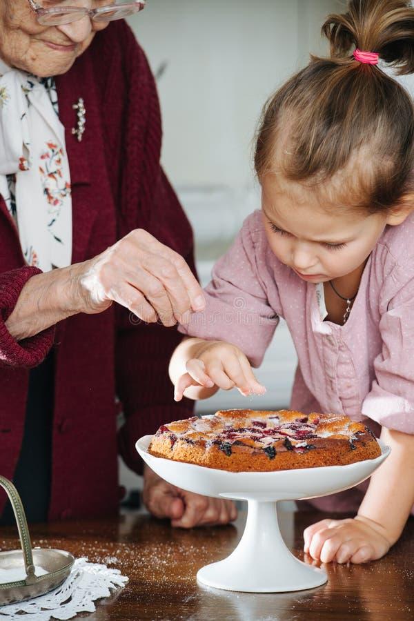 Mulher superior junto com sua neta que derrama o açúcar pulverizado na torta saboroso foto de stock
