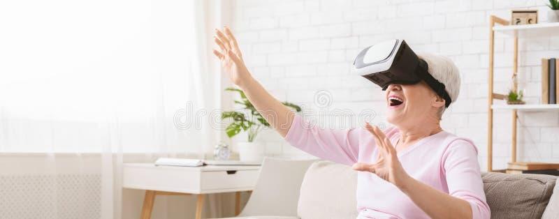 Mulher superior moderna que usa vidros de VR em casa fotografia de stock