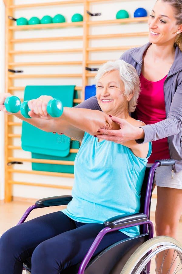 Mulher superior na cadeira de roda que faz a fisioterapia imagem de stock