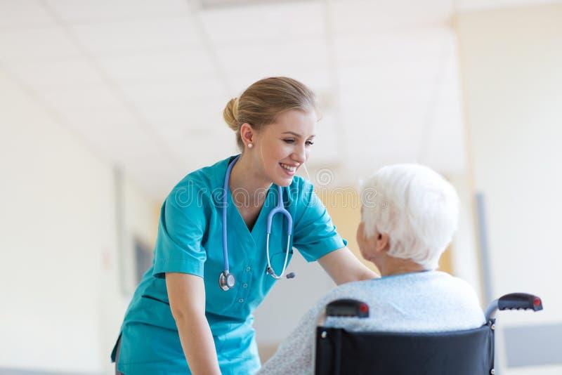 Mulher superior na cadeira de rodas com a enfermeira no hospital foto de stock royalty free