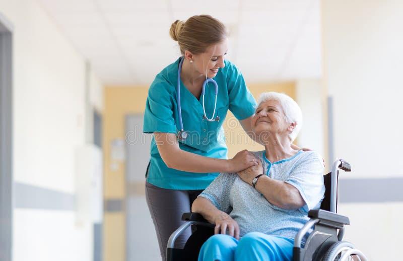Mulher superior na cadeira de rodas com a enfermeira no hospital fotos de stock