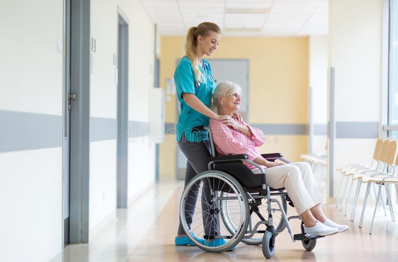 Mulher superior na cadeira de rodas com a enfermeira no hospital imagens de stock