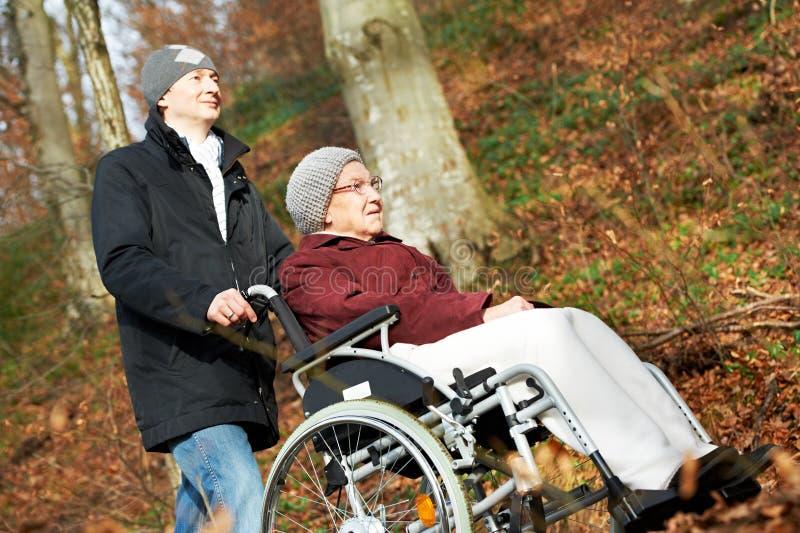 Mulher superior na cadeira de rodas e no filho no parque fotografia de stock royalty free