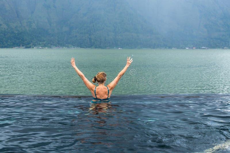 Mulher superior na piscina da natureza com fundo surpreendente da montanha Ilha tropical Bali, Indonésia fotografia de stock