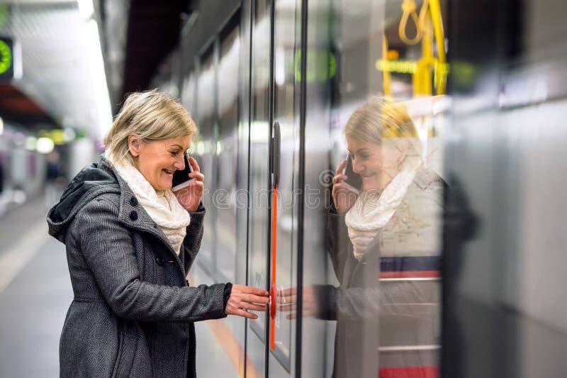 Mulher superior na plataforma subterrânea, falando no telefone imagens de stock royalty free