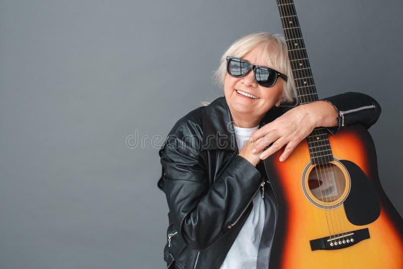 Mulher superior na posição do estúdio do casaco de cabedal e dos óculos de sol no sonho de aperto cinzento da guitarra alegre imagens de stock royalty free