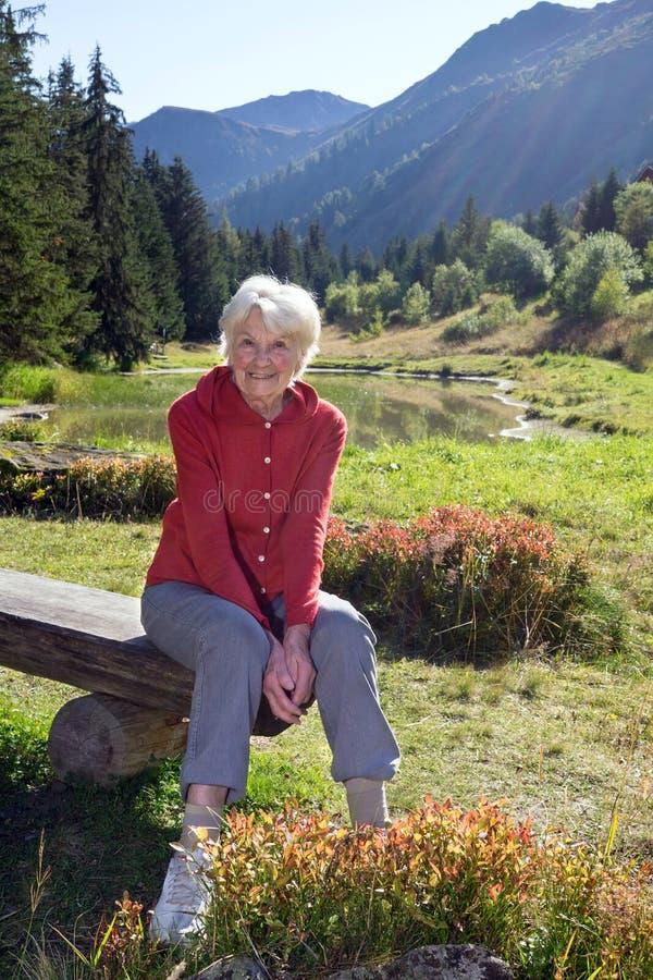 Mulher superior no banco pelo lago nas montanhas fotografia de stock