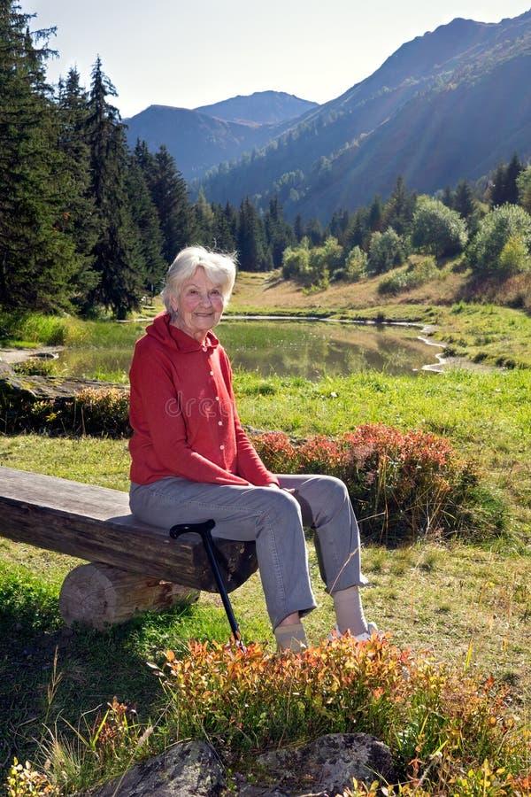 Mulher superior no banco perto do lago nas montanhas imagens de stock