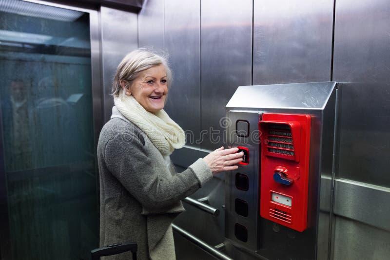 Mulher superior no elevador na viagem do estação de caminhos-de-ferro fotos de stock royalty free