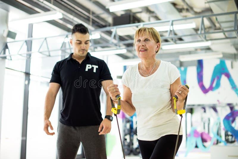 Mulher superior no gym, exercício do susspension imagens de stock