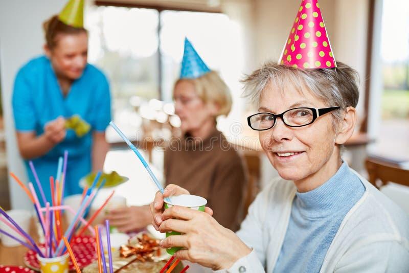Mulher superior no lar de idosos que comemora o carnaval fotos de stock royalty free