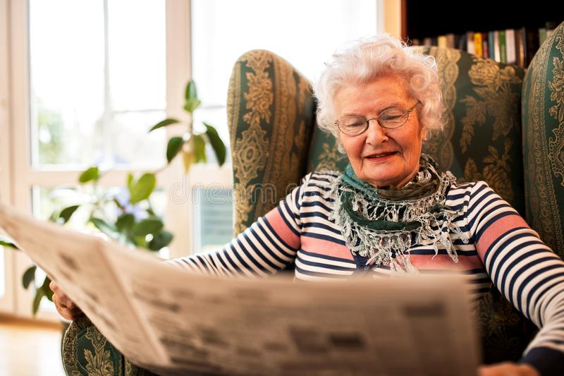 Mulher superior no pansion que relaxa em casa ao ler um newspap imagem de stock royalty free