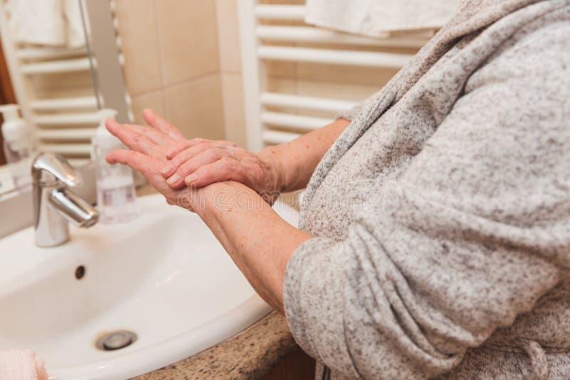 Mulher superior no roupão que aplica o creme da mão no banheiro, close up foto de stock royalty free