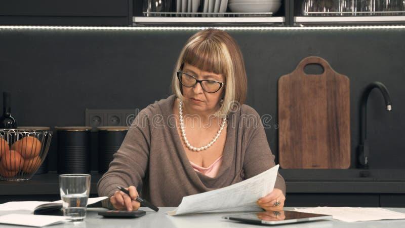 A mulher superior nos vidros considera despesas imagens de stock royalty free