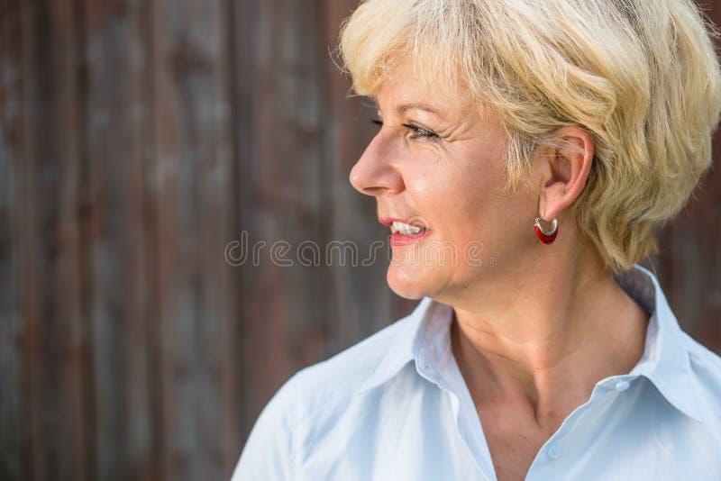 Mulher superior nostálgica que olha afastado com um sorriso quando daydreami fotografia de stock