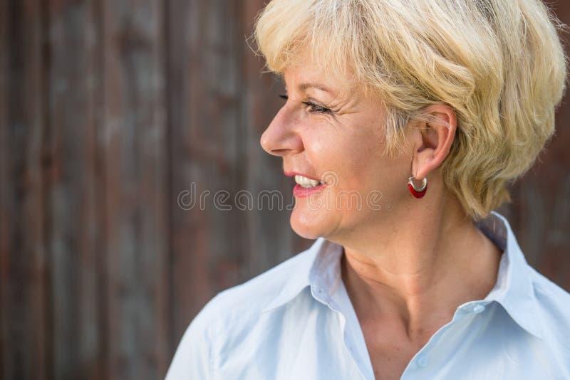 Mulher superior nostálgica que olha afastado com um sorriso quando daydreami imagens de stock royalty free