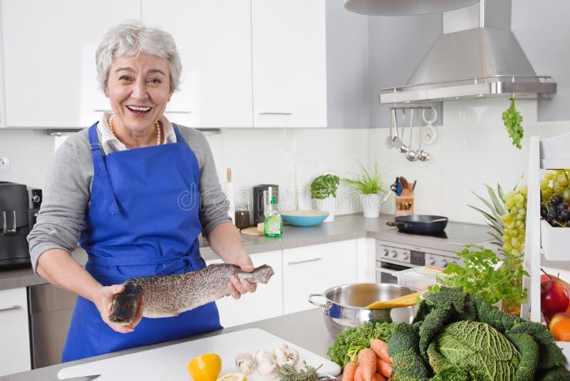 Mulher superior ou mais idosa com cabelo cinzento que cozinha na cozinha - fresca foto de stock