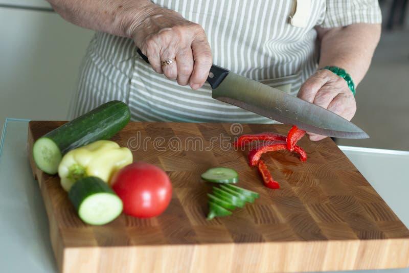 Mulher superior ou mais idosa que cozinha a salada na cozinha Conceito saud?vel do alimento Estilo de vida saud?vel A avó prepara fotografia de stock