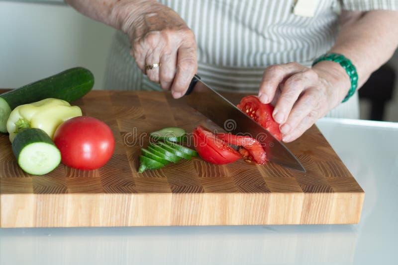 Mulher superior ou mais idosa que cozinha a salada na cozinha Conceito saud?vel do alimento Estilo de vida saud?vel A avó prepara fotos de stock