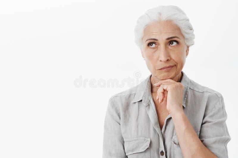 Mulher superior pensativa e sábia desagradada com cabelo cinzento que smirking da vista de pensamento do desagrado e do irritatio imagem de stock