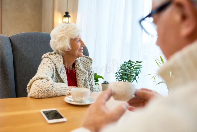 Mulher superior pensativa na tabela no café imagens de stock