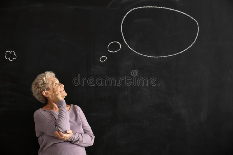 Mulher superior perto do quadro escuro com bolha vazia do discurso fotos de stock
