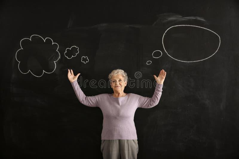 Mulher superior perto do quadro escuro com bolhas vazias do discurso foto de stock royalty free