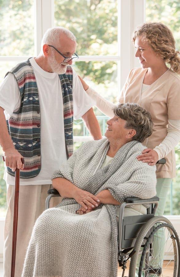 Mulher superior positiva na cadeira de rodas com enfermeira de inquietação e o amigo idoso com vara de passeio fotos de stock