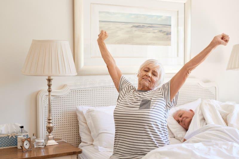 Mulher superior que acorda com um estiramento na manhã foto de stock royalty free