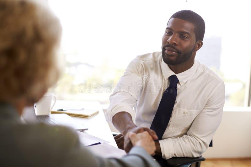 Mulher superior que agita as mãos com o cirurgião masculino In Office do doutor Financial Advisor Cosmetic imagem de stock