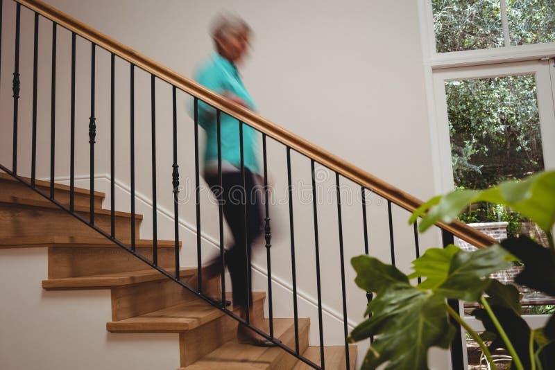 Mulher superior que anda abaixo das escadas fotografia de stock royalty free