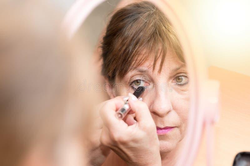 Mulher superior que aplica o lápis de olho, efeito da luz imagens de stock royalty free