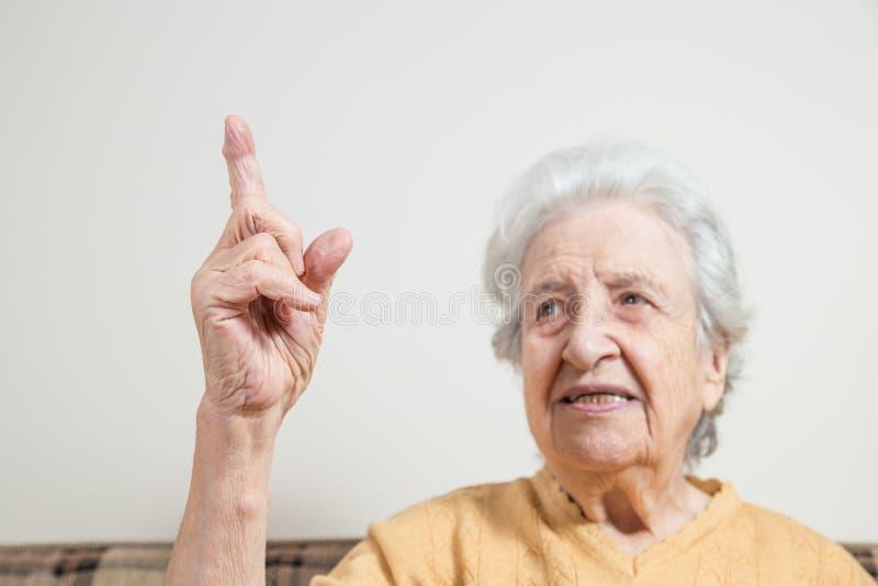 Mulher superior que aponta algo imagem de stock