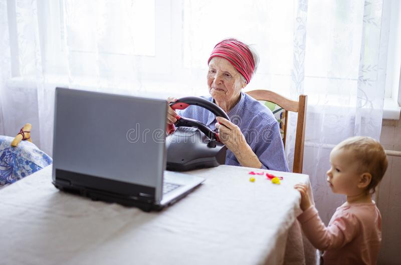 Mulher superior que aprecia o jogo de vídeo das corridas de carros no portátil quando seu grande - neta que olha seu jogo imagem de stock