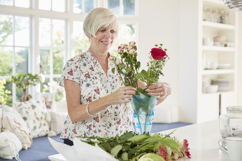 Mulher superior que arranja flores em casa fotografia de stock