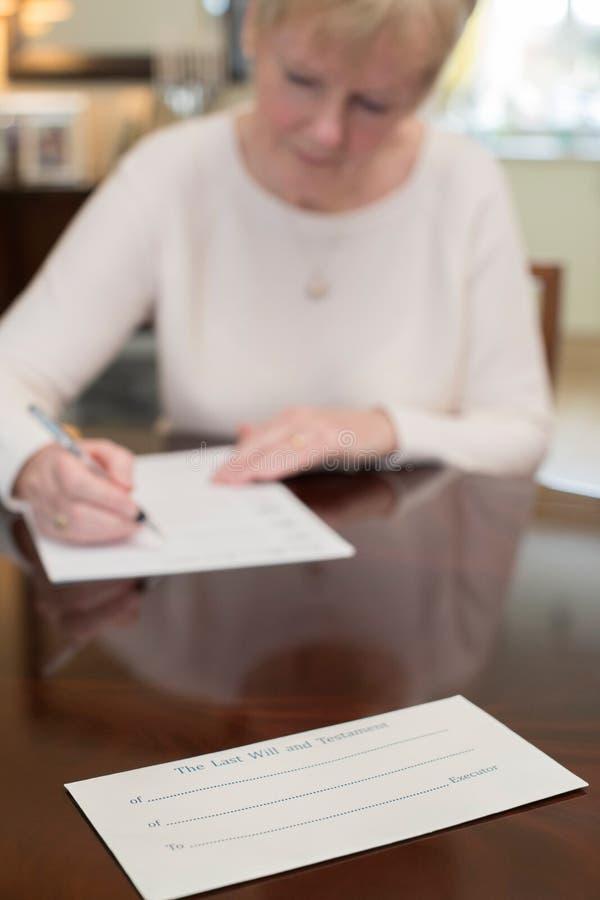A mulher superior que assina por último e testamento em casa fotografia de stock royalty free