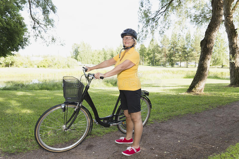 Mulher superior que bicycling em um parque na tarde ensolarada foto de stock