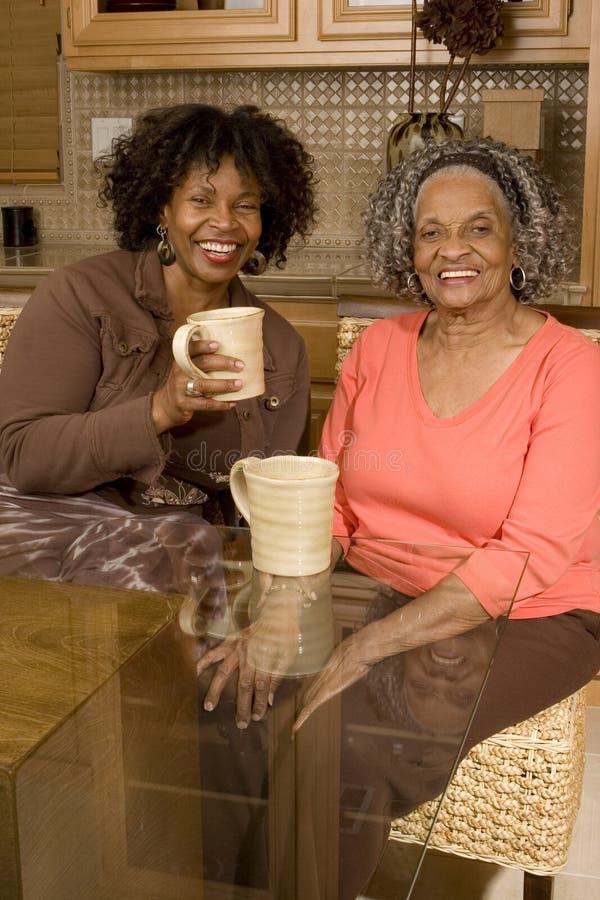Mulher superior que come o café com sua filha fotografia de stock