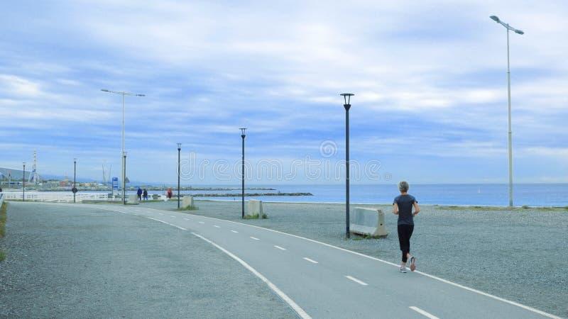 Mulher superior que corre em um passeio contra um céu nebuloso azul Conceito ativo do envelhecimento e espaço vazio da cópia imagens de stock