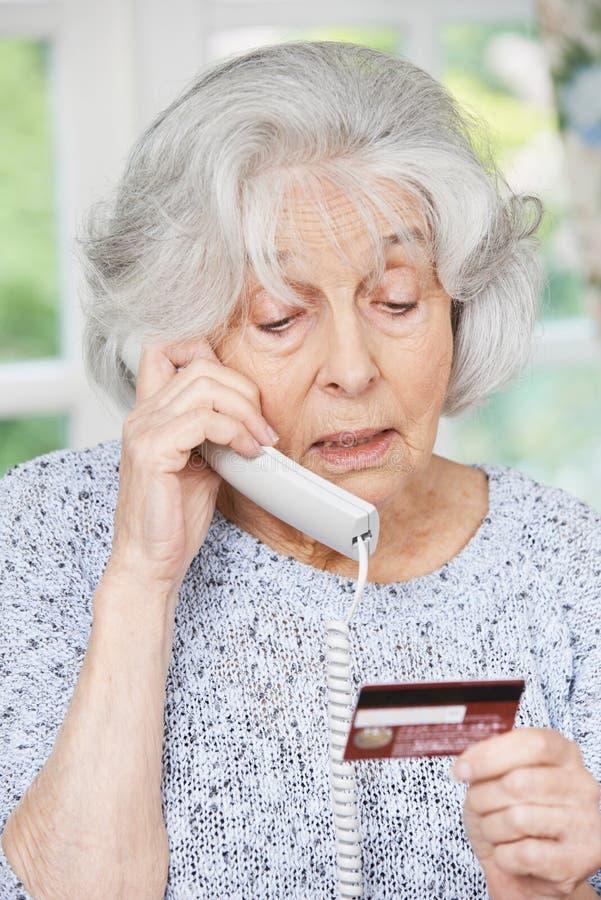 Mulher superior que dá detalhes do cartão de crédito no telefone fotos de stock royalty free