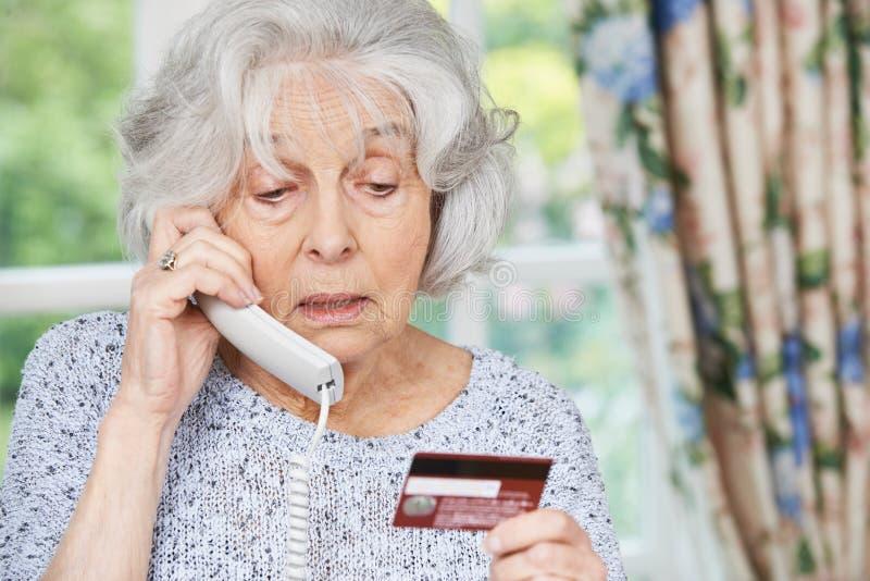 Mulher superior que dá detalhes do cartão de crédito no telefone foto de stock royalty free