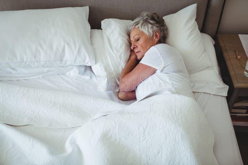 Mulher superior que dorme na cama no quarto imagem de stock royalty free