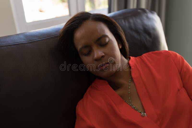 Mulher superior que dorme na sala de visitas fotografia de stock