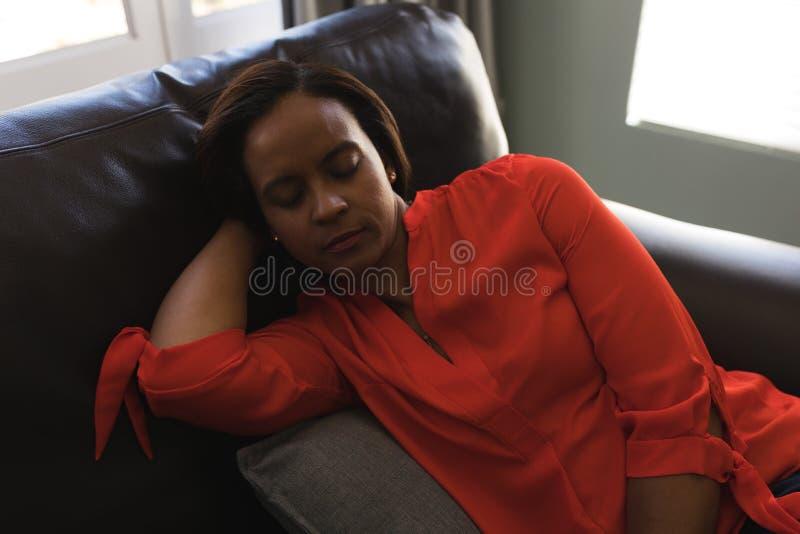 Mulher superior que dorme na sala de visitas imagens de stock royalty free