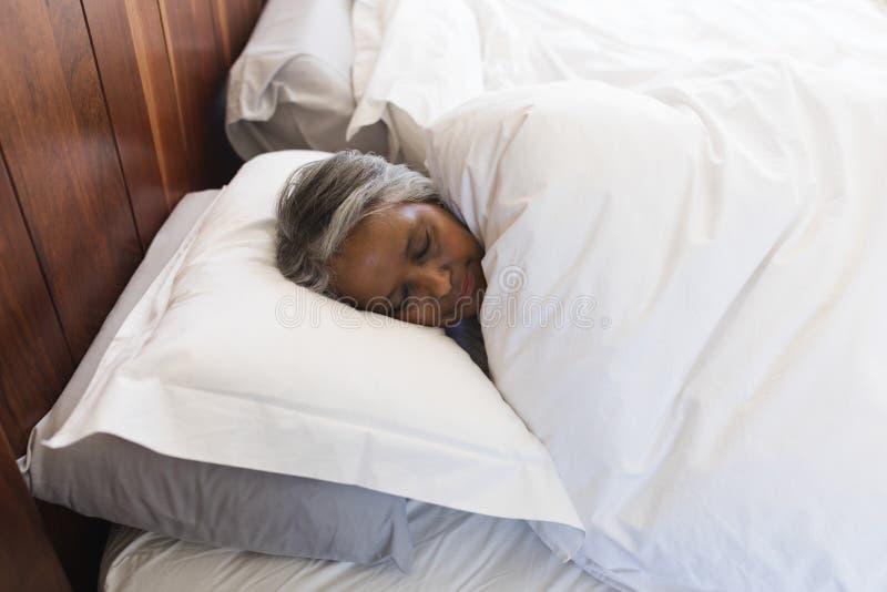 Mulher superior que dorme no quarto em casa imagem de stock