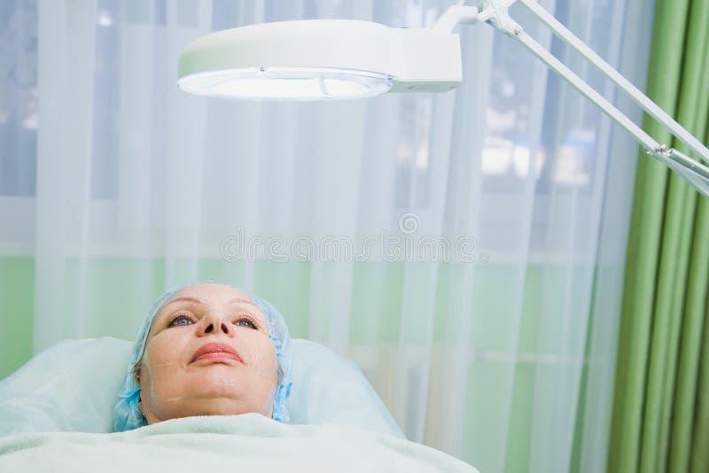 Mulher superior que encontra-se no sofá médico na clínica da cosmetologia fotografia de stock royalty free