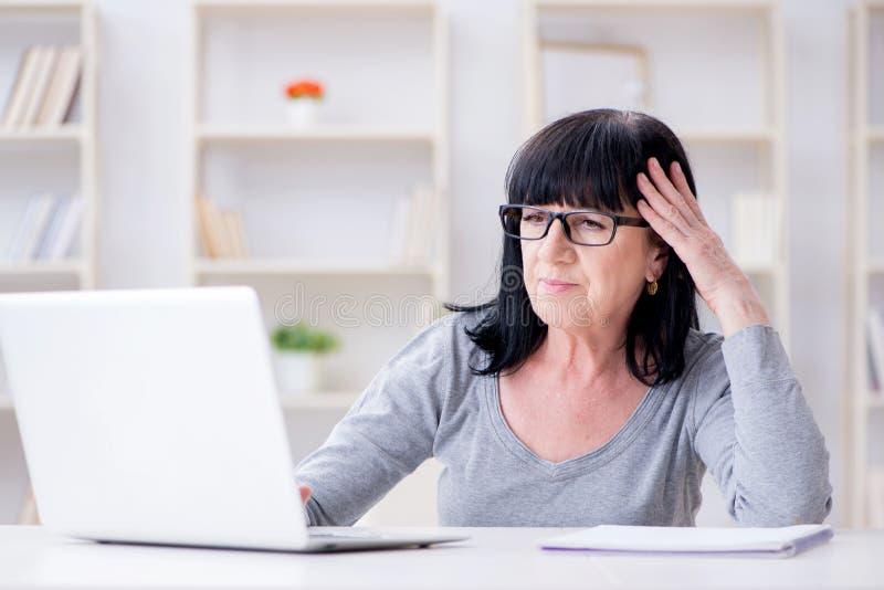 A mulher superior que esforça-se no computador fotografia de stock